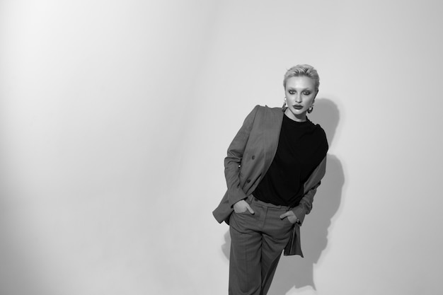 Élégante jeune femme en costume en studio sur fond blanc. coupe de cheveux courte. photo noir et blanc Photo Premium