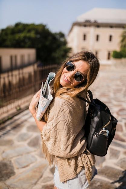 Élégante jeune femme debout dans la rue tenant la carte Photo gratuit