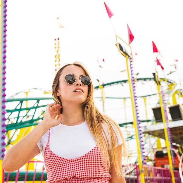 Élégante jeune femme debout devant les montagnes russes Photo gratuit