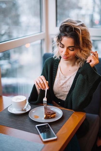 Élégante jeune femme avec dessert et tasse de boisson près smartphone à table Photo gratuit