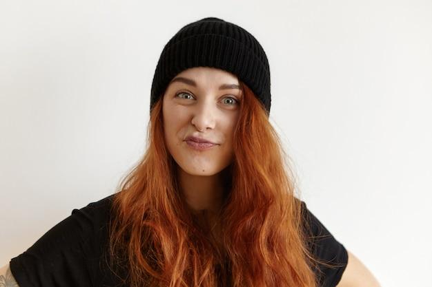 Élégante Jeune Femme Européenne Avec Une Coiffure En Désordre Portant Un Chapeau Noir Et Un T-shirt Boudeur Photo gratuit