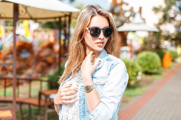 Élégante Jeune Femme Hipster à La Mode Dans Des Lunettes De Soleil En Veste En Jean D'été Bleu à La Mode En Chemisier En Dentelle Blanche Vintage Sur Une Promenade Dans Un Parc D'attractions Photo Premium