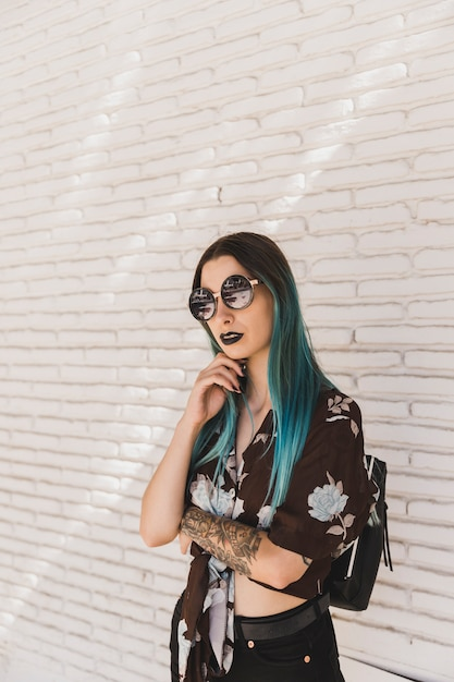 Élégante jeune femme avec des lunettes de soleil posant devant le mur Photo gratuit