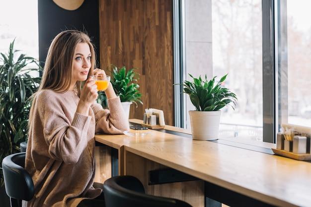 Élégante jeune femme positive tenant la tasse de boisson au comptoir près de la fenêtre au café Photo gratuit