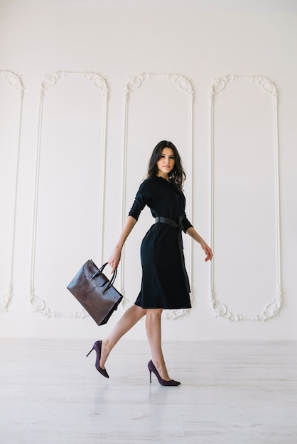Élégante jeune femme en robe avec sac à main posant dans la chambre Photo gratuit