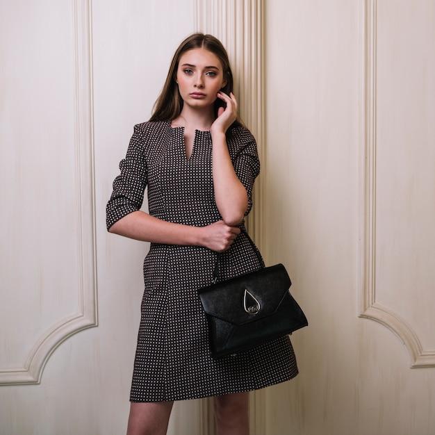 Élégante jeune femme en robe avec sac à main tenant joue dans la chambre Photo gratuit