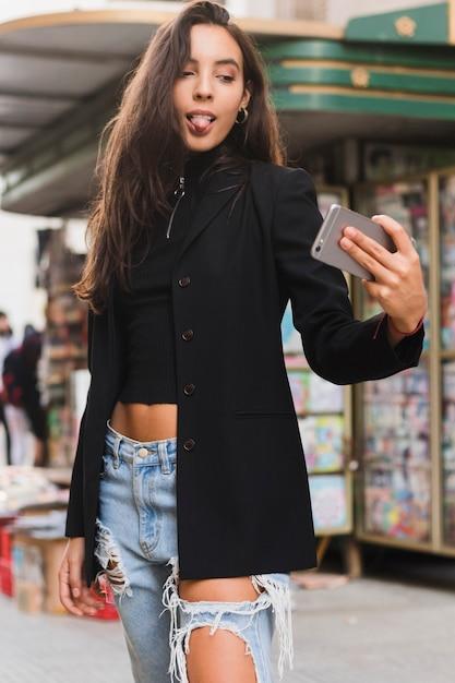 Élégante jeune femme tire la langue tout en prenant selfie sur téléphone mobile Photo gratuit