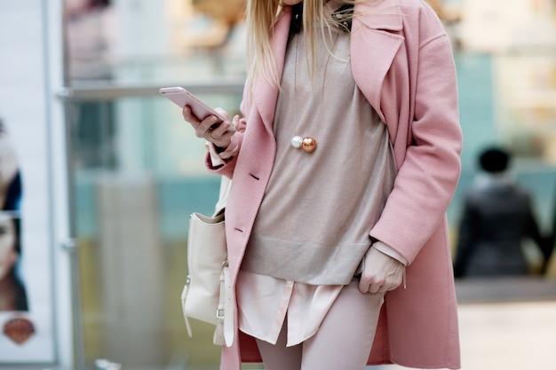 Élégante jeune fille debout dans un manteau rose dans un magasin et regarder dans le téléphone Photo Premium