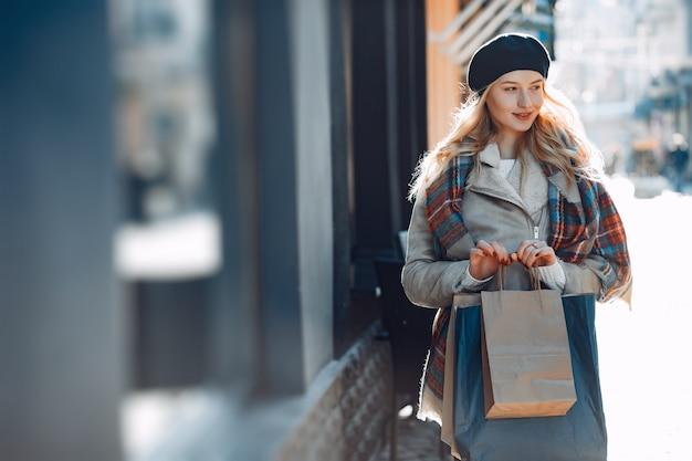 Elégante jolie blonde marchant dans une ville Photo gratuit