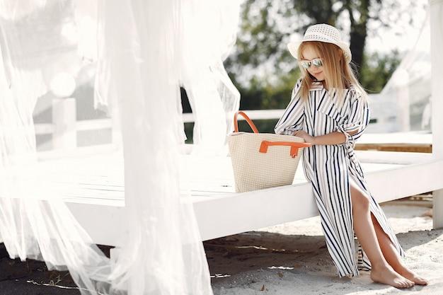 Élégante petite fille sur une côte d'été Photo gratuit
