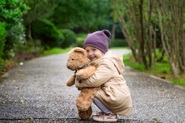 Élégante petite fille embrassant son ours en peluche en automne parc Photo Premium
