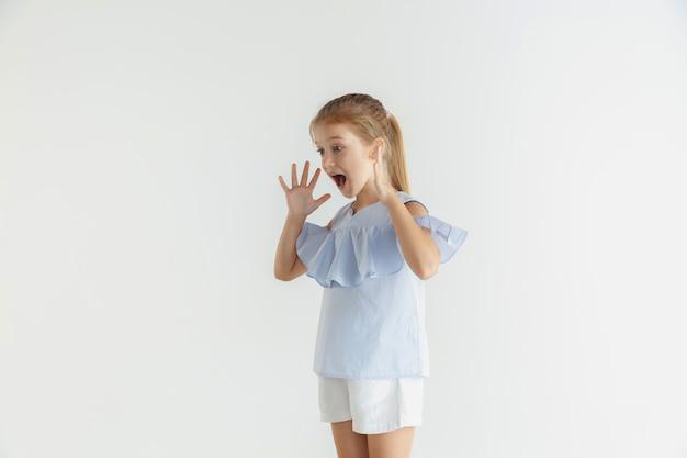 Élégante Petite Fille Souriante Posant Dans Des Vêtements Décontractés Isolés. Modèle Féminin Blonde Caucasienne. émotions Humaines, Expression Faciale, Enfance. Choqué, étonné. Photo gratuit