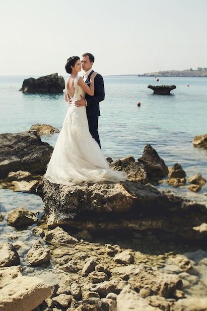 Élégante, Souriante Jeune Mariée Et Mariée Posant Sur Les Rochers Sur La Plage Photo gratuit