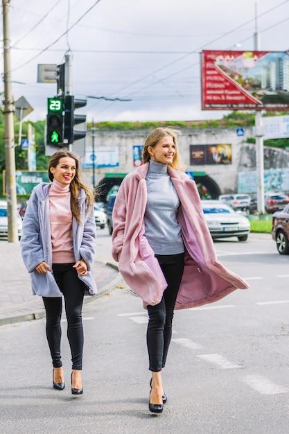 Élégantes Deux Jeunes Femmes En Veste De Fourrure Traversant La Route Photo gratuit
