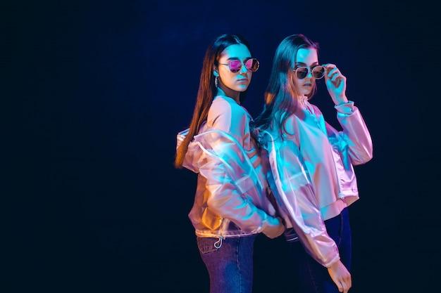 Élégantes jeunes femmes posant dans la lumière néon Photo Premium