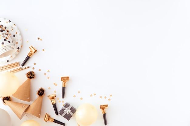 Éléments de la fête dorée avec des confettis sur fond blanc Photo Premium