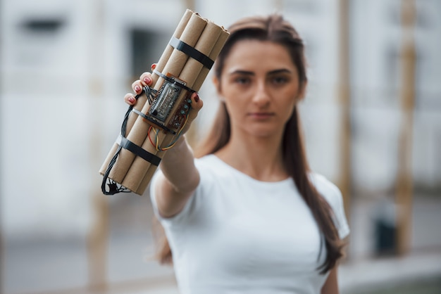 Éléments Numériques. Montrant Une Bombe à Retardement. Jeune Femme Tenant Une Arme Explosive Dangereuse Dans La Main Photo gratuit