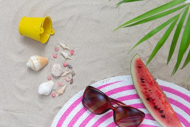 Éléments de plage sur le sable avec melon d'eau et lunettes de soleil Photo gratuit
