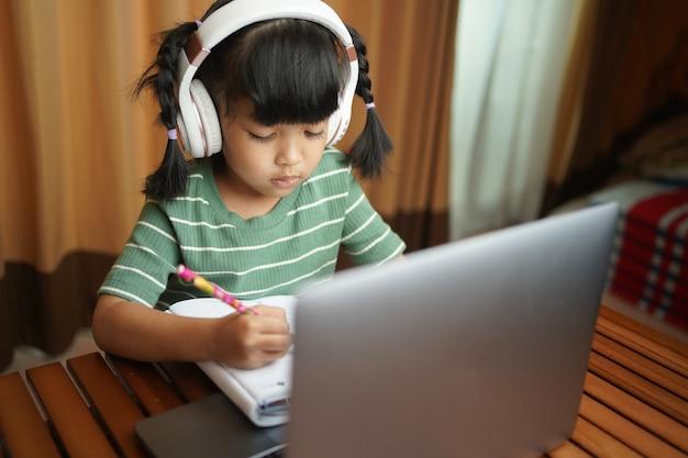 Élève De L'école Enfant Fille Asiatique Portant Des écouteurs étudiant En Ligne à La Maison En Regardant Le Cours De Classe Web Ou En écoutant Le Tuteur Par Appel Vidéo Photo Premium