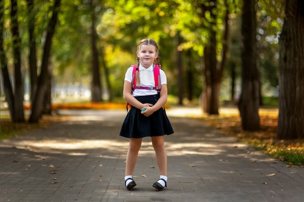 Elève D'école Primaire. Fille Avec Sac à Dos à L'extérieur. Début Des Cours. Premier Jour D'automne Photo Premium