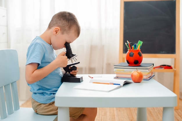 L'élève est assis à table et engagé dans du matériel éducatif. écolier regarde à travers un microscope. Photo Premium