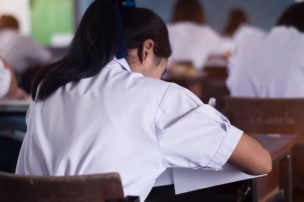 Élève prend un examen et écrit la réponse en salle de classe pour le concept de test de l'éducation. Photo Premium