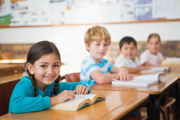 Élèves assis dans la salle de classe en lisant des livres Photo Premium