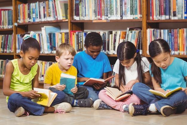 Élèves Assis Par Terre Et Lisant Des Livres Dans La Bibliothèque Photo Premium