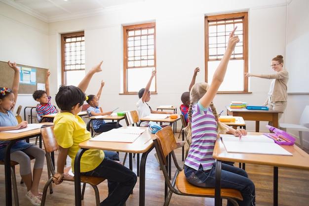 Élèves levant la main dans la salle de classe Photo Premium