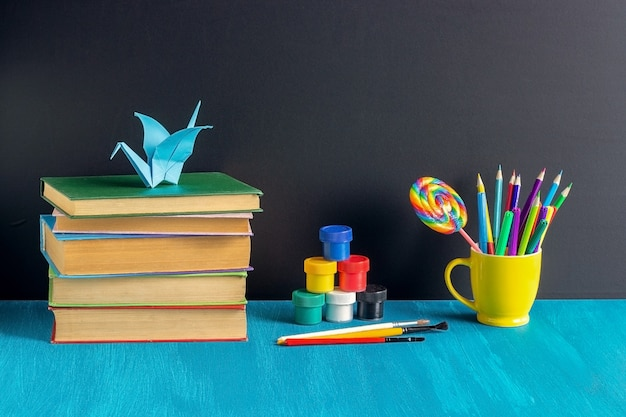 Elèves sur le lieu de travail. livres, papeterie, peinture, gouache et grue en origami sur table bleue Photo Premium