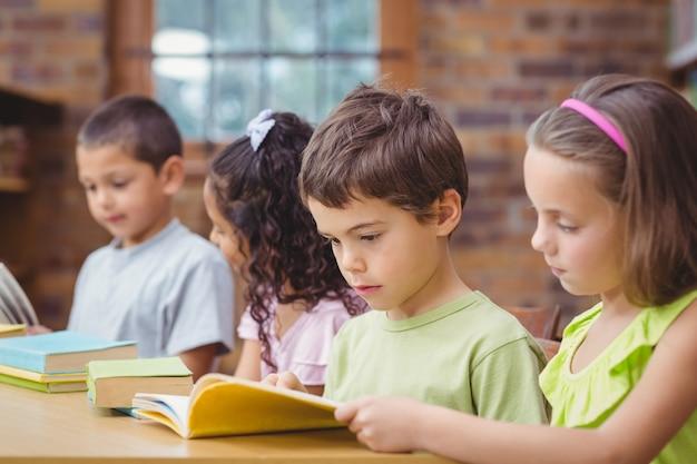 Elèves lisant des livres dans une bibliothèque Photo Premium