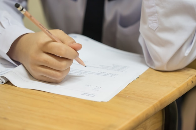 Élèves utilisant un crayon lisant des informations sur du papier blanc au lycée Photo Premium