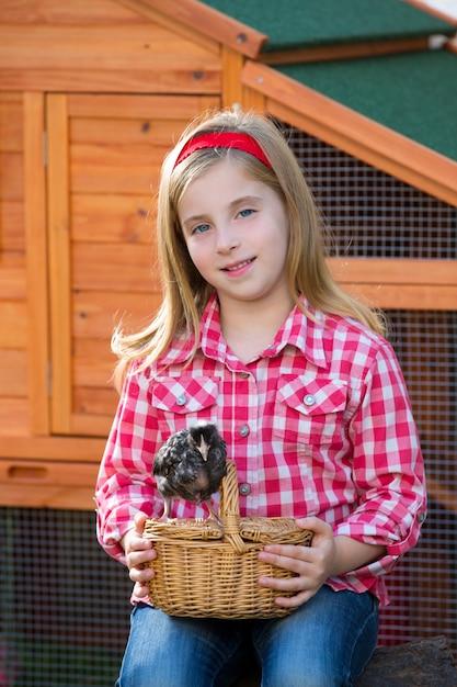 Éleveur poules enfant fille fermier éleveur avec poussins au poulailler Photo Premium