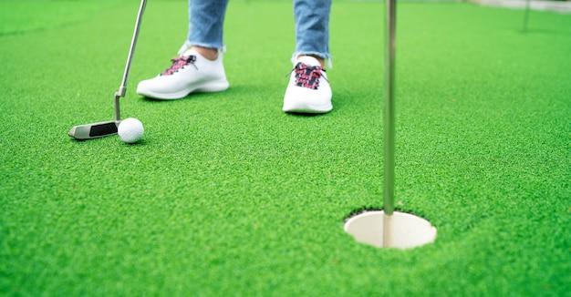 Elle joue au golf dans un gazon artificiel. Photo Premium