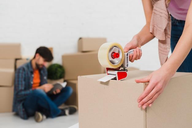 Emballage des boîtes avec du ruban de construction afin d'emménager dans de nouveaux logements Photo gratuit