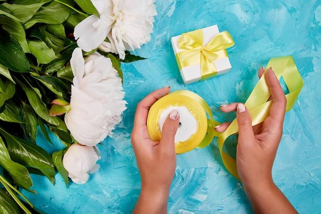 Emballage Cadeau Femme Blanche Avec Ruban Jaune Près De Fleurs Blanches Photo Premium