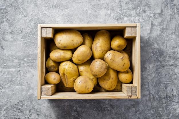 Emballage écologique pour les légumes, sans plastique. pommes de terre dans une boîte en bois, supermarché. Photo Premium