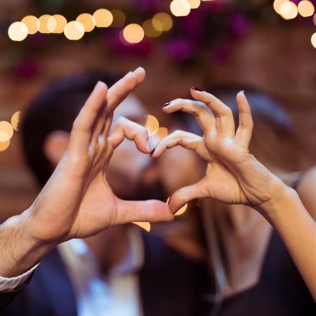 Embrasser couple montrant le symbole du coeur Photo gratuit