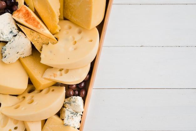 L'emmental; bleu; fromage cheddar avec des olives dans un plateau sur un bureau blanc Photo gratuit