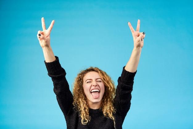 Émotif Satisfait Jeune Femme Frisée Attrayante Au Gingembre Avec La Bouche Ouverte Pour Célébrer Et Encourager Un Succès En Levant Les Mains Photo Premium