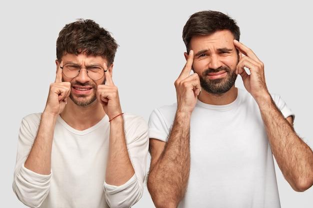 Émotions Et Expressions Faciales Humaines Négatives. Les Hommes Mécontents Gardent Leurs Doigts Sur Les Tempes, Froncent Les Sourcils En Signe De Mécontentement, Souffrent De Maux De Tête, Portent Des Vêtements Décontractés Photo gratuit