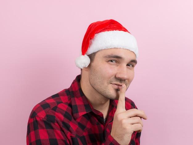 Émotions sur le visage, colère, méchanceté, bandit, complot du mal. un homme dans un lapin à carreaux et un chapeau de noël rouge Photo Premium