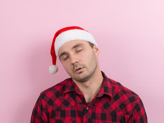 Émotions sur le visage, fatigue, gueule de bois de vacances, prise de conscience. un homme dans un lapin à carreaux et un chapeau de noël rouge Photo Premium