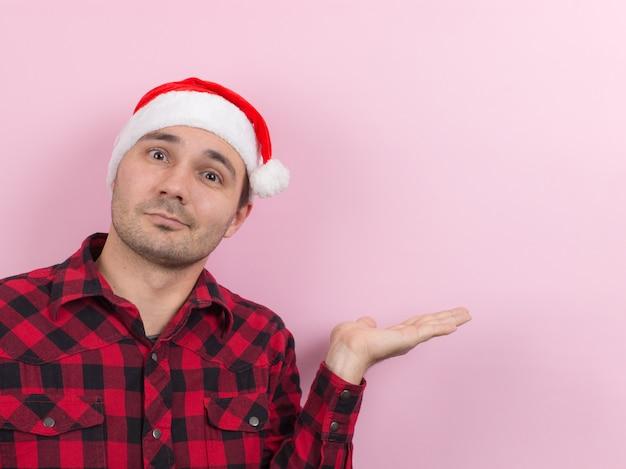 Émotions sur le visage, sourire, joie. un homme dans un lapin à carreaux et un chapeau de noël rouge Photo Premium