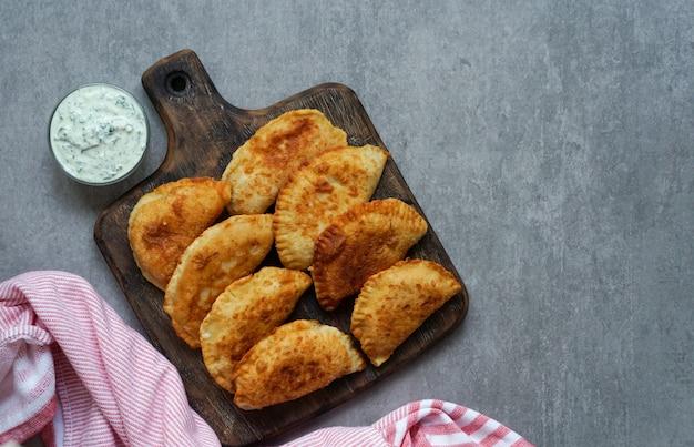 Empanadas frites espagnoles et latino-américaines avec sauce sur pierre grise Photo Premium