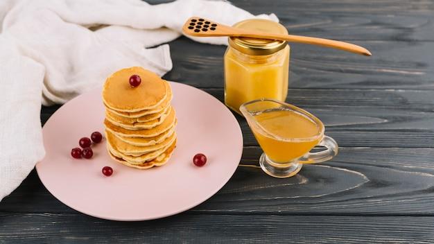 Empilé de crêpes et de baies de cassis rouge avec du lait caillé au citron sur fond en bois Photo gratuit