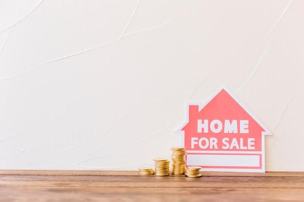 Empilé des pièces de monnaie avec maison à vendre icône s'appuyant sur le mur Photo gratuit