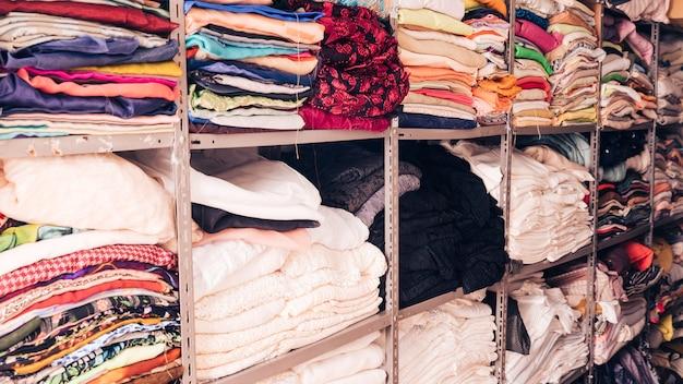 Empilé de tissus colorés dans l'étagère Photo gratuit