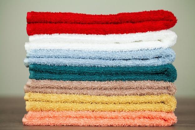 Empiler des serviettes colorées dans la salle de bain sur la table Photo Premium
