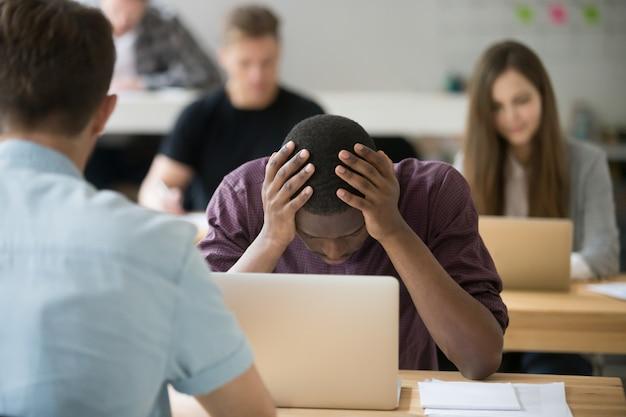 Employé de bureau africain frustré ayant des difficultés à tenir la tête dans les mains Photo gratuit